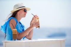 Ung flicka som dricker kallt kaffe som tycker om havssikt Den härliga kvinnan kopplar av under exotisk semester på stranden som t Arkivbild