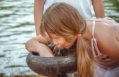Ung flicka som dricker på springbrunnen royaltyfri fotografi