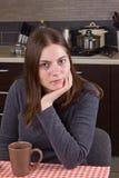 Ung flicka som dricker te på kök Royaltyfria Bilder