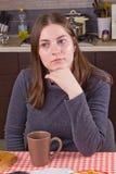 Ung flicka som dricker te på kök Arkivfoton