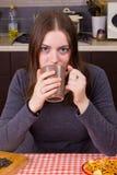 Ung flicka som dricker te på kök Fotografering för Bildbyråer