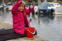 Ung flicka som fångar krabbor på ferie Arkivbilder