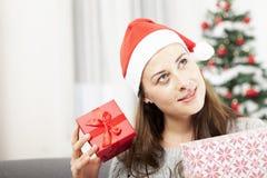 Ung flicka som får förvånad av julgåvan Arkivfoto