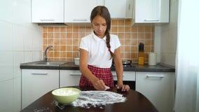 Ung flicka som förbereder funktionsduglig yttersida för deg som knådar fördelande mjöl på den mörka tabellen i kök arkivfilmer
