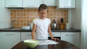 Ung flicka som förbereder funktionsduglig yttersida för deg som knådar fördelande mjöl på den mörka tabellen i kök lager videofilmer