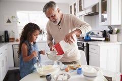 Ung flicka som förbereder kakablandningen med hennes farfar på köksbordet, slut upp arkivbild