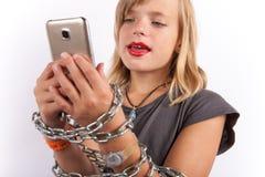 Ung flicka som fjättras med en chain användande smartphone royaltyfri bild