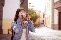 Ung flicka som fokuserar hennes gamla kamera Royaltyfria Foton