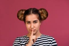 Ung flicka som frågar för tystnad eller sekretess med fingret på kantshh teckengest över rosa bakgrund hyssja royaltyfria bilder