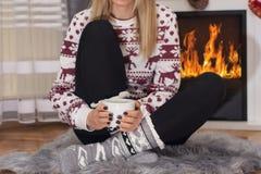 Ung flicka som framme sitter av spisen och rymmer kopp te i hand på ben och värme royaltyfri foto