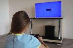 Ung flicka som framme spelar av TV:N royaltyfri foto