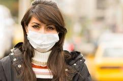 Ung flicka som går bära en maskering i staden Fotografering för Bildbyråer