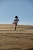 Ung flicka som går i öknen Arkivfoto
