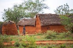 Ung flicka som går i den traditionella afrikanska byn, Kenya Arkivfoton