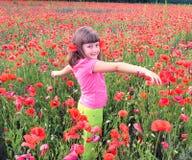 Ung flicka som går in i fält av vallmo Royaltyfria Bilder