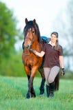 Ung flicka som går med en utomhus- häst Fotografering för Bildbyråer