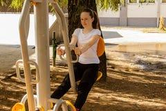 Ung flicka som gör övningar som är utomhus- på solig dag Fotografering för Bildbyråer