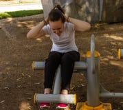 Ung flicka som gör övningar för buk- muskler Fotografering för Bildbyråer