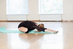 Ung flicka som gör övningar i dansgrupp Arkivfoto