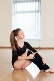 Ung flicka som gör övningar i dansgrupp Arkivbild