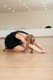 Ung flicka som gör övningar i en dansgrupp Arkivfoto