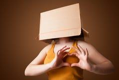 Ung flicka som gör en gest med en kartong på hans huvud Arkivbild