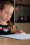 Ung flicka som gör läxa på köksbordet Royaltyfria Foton