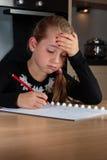 Ung flicka som gör läxa på köksbordet Arkivfoto