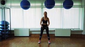 Ung flicka som gör sportövning genom att använda hanteln på idrottshallen royaltyfria bilder