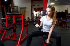 Ung flicka som gör sporten i en stor idrottshall arkivbilder