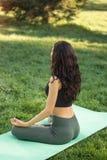 Ung flicka som gör yoga i parkera Fotografering för Bildbyråer