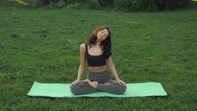 Ung flicka som gör yoga i parkera stock video