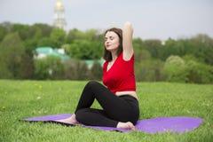 Ung flicka som gör yoga i parkera Arkivfoton