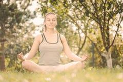 Ung flicka som gör yoga i parkera Arkivfoto