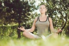 Ung flicka som gör yoga i parkera Royaltyfria Foton
