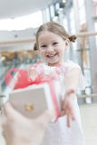 Ung flicka som ger en gåva Royaltyfria Foton