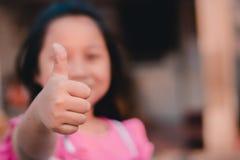 Ung flicka som ger upp tummen arkivbild