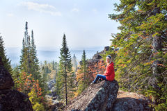 Ung flicka som har en vila upptill av berget Lugna begrepp meditation Älska för natur royaltyfri bild