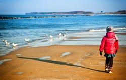 Ung flicka som har gyckel på den baltiska stranden för vinter Royaltyfri Foto