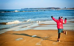 Ung flicka som har gyckel på den baltiska stranden för vinter Arkivbild