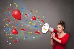 Ung flicka som har gyckel som ropar in i megafonen med ballonger Royaltyfri Bild