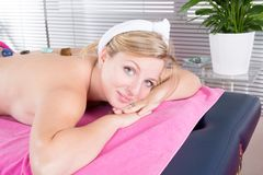 Ung flicka som har massage med stenar i brunnsortsalong Arkivbilder
