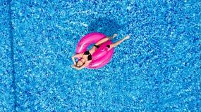 Ung flicka som har roligt och skrattar och har gyckel i pölen på en uppblåsbar rosa flamingo i en baddräkt i sommar från abov royaltyfri fotografi