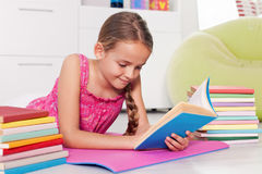 Ung flicka som hemma läser en bok Royaltyfri Bild