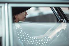 Ung flicka som kör en retro bil arkivfoto