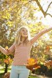 Ung flicka som kastar Autumn Leaves In The Air fotografering för bildbyråer