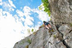 Ung flicka som klättrar en stege fotografering för bildbyråer