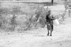 Ung flicka som kommer med en hink för att ta vatten Arkivfoton
