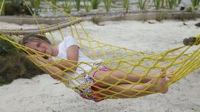Ung flicka som kopplar av i en hängmatta på havsstranden arkivfilmer