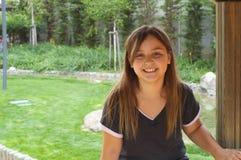 Ung flicka som kopplar av i trästruktur Arkivbild